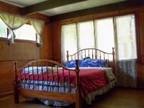 Brush Lodge back bedroom has beamed ceiling and large brick fireplace with own 1/2 bath